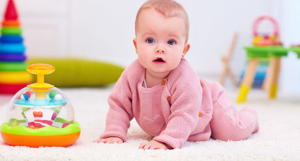 cute little baby girl crawling on the carpet among the development toys at a Preschool & Daycare Serving Greenville, AL