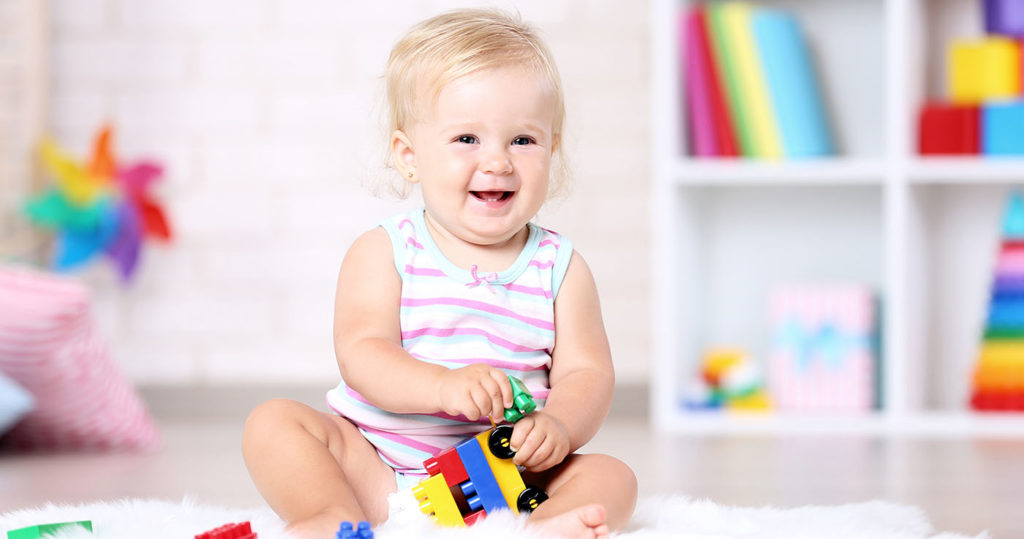 Baby girl sitting on white carpet with toy blocks at a Preschool & Day
