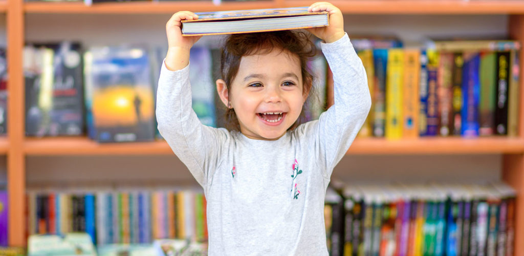 Cute Young TodCute Young Toddler Standing and Holding Book in Head. Little Happy Laughing Girl Indoors In Front Of Colorful Books. Child in a Library, Shop,Bookstore.dler Standing and Holdi ng Book in Head. Little Happy Laughing Girl Indoors In Front Of Colorful Books. Child in a Library, Shop,Bookstore at a Preschool & Daycare Serving Greenville, AL