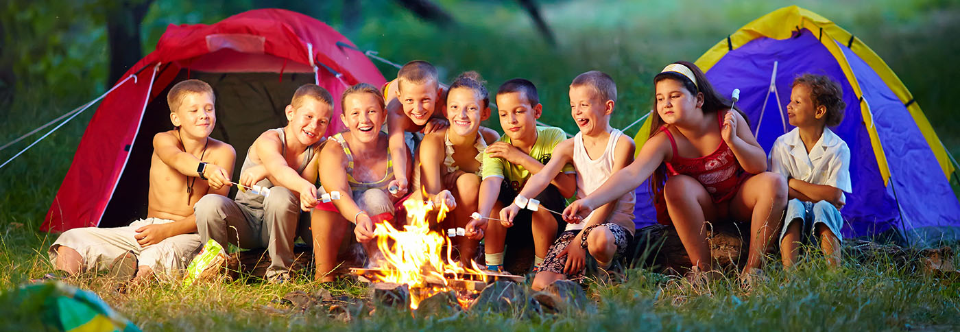 Group of kids toasting a marshmallow on a bonfire outdoors sitting in front of tents at a Preschool & Daycare Serving Greenville, AL
